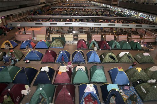 AP Photo - Evacuees from floodwaters rest in tents at an evacuation center in Bangkok
